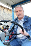 Farmer driving tractor Stock Photo