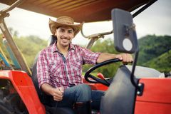 Farmer driving tractor in the fields during harvest in countryside. worker sitting on his tractor smiling. stock photo