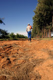 Farmer in drought. Farmer walking on try ground, worrying about the drought Stock Photography