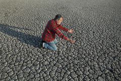 Farmer and drought in field. Desperate man kneeling at dry cracked land after drought, natural disaster Stock Images