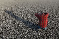Farmer and drought in field. Desperate man kneeling and holding his head in his hands at dry cracked land after drought, natural disaster Stock Photo