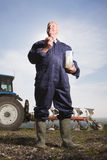 Farmer eating lunch in field with tractor and plough in background Stock Image