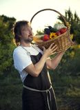 Farmer with an ecological harvest of vegetables in a basket near. The garden beds in summer Stock Photography