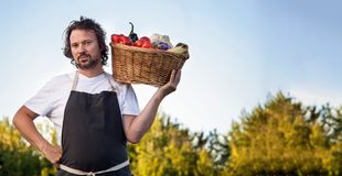 Farmer with an ecological harvest of vegetables in a basket near stock photo