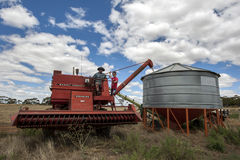 A farmer empties grain from his harvester into a field silo. Stock Image
