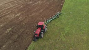 Farmer on an energy saturated tractor produces plowing with a turnover of the soil layer with a modern plow in cloudy