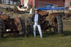 Farmer with Equipment. Farmer poses in front of old tractors out in the barnyard royalty free stock photo