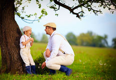 Farmer family having fun under an old tree, spring countryside Royalty Free Stock Images