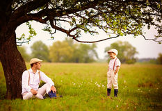 Farmer family having fun under an old tree, spring countryside Stock Photography