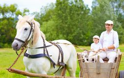 Farmer family riding a horse cart. focus on horse Royalty Free Stock Image