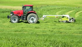 Farmer Farming Tractor Hay. Farmer in his tractor cutting grass for hay Royalty Free Stock Image