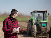 Farmer on the farmland. Young farmer supervising work on farmland, tractor harrowing in background Stock Photography