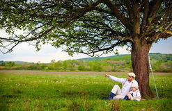 Farmer father and son sitting under the tree, spring countryside Royalty Free Stock Image