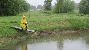 Farmer feed fish rain stock video footage