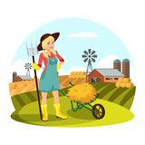 Woman with pitchfork in front of field with hay. Farmer female with pitchfork gathering hay in front of field with barns and round hay bale. Woman work at Stock Photos