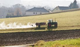 Farmer fertilizes the meadow with dung Stock Photography