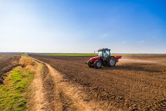 Farmer fertilizing arable land. With nitrogen, phosphorus, potassium fertilizer Royalty Free Stock Image