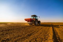 Farmer fertilizing arable land. With nitrogen, phosphorus, potassium fertilizer Stock Image