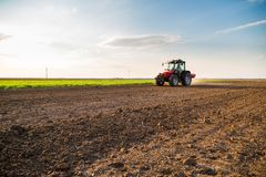 Farmer fertilizing arable land with nitrogen, phosphorus, potassium fertilizer. Agricultural activity Royalty Free Stock Photos