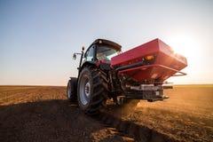 Farmer fertilizing arable land with nitrogen, phosphorus, potassium fertilizer. Agricultural activity Royalty Free Stock Photography