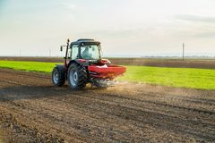 Farmer fertilizing arable land with nitrogen, phosphorus, potassium fertilizer. Agricultural activity Stock Photography