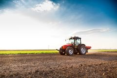 Farmer fertilizing arable land with nitrogen, phosphorus, potassium fertilizer. Agricultural activity Stock Photos