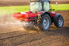 Farmer fertilizing arable land with nitrogen, phosphorus, potassium fertilizer. Agricultural activity Stock Image