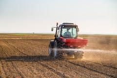 Farmer fertilizing arable land. With nitrogen, phosphorus, potassium fertilizer Stock Photo