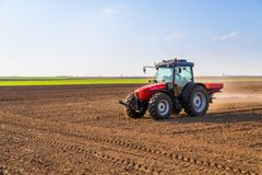 Farmer fertilizing arable land. With nitrogen, phosphorus, potassium fertilizer Stock Photos