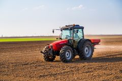 Farmer fertilizing arable land. With nitrogen, phosphorus, potassium fertilizer Stock Images