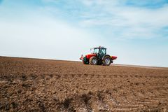 Farmer fertilizing arable land with nitrogen, phosphorus, potassium fertilizer.  Royalty Free Stock Image
