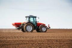 Farmer fertilizing arable land with nitrogen, phosphorus, potassium fertilizer.  Royalty Free Stock Photos
