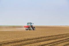 Farmer fertilizing arable land with nitrogen, phosphorus, potassium fertilizer. Agricultural activity Royalty Free Stock Image