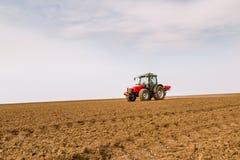 Farmer fertilizing arable land with nitrogen, phosphorus, potassium fertilizer.  Stock Images