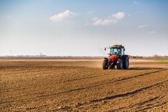 Farmer fertilizing arable land with nitrogen, phosphorus, potassium fertilizer. Agricultural activity Stock Photos