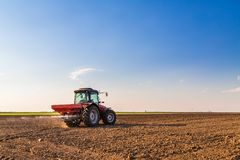 Farmer fertilizing arable land with nitrogen, phosphorus, potassium fertilizer. Agricultural activity Royalty Free Stock Images