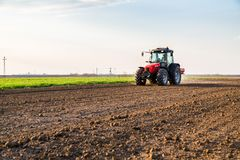 Farmer fertilizing arable land with nitrogen, phosphorus, potassium fertilizer. Agricultural activity Royalty Free Stock Images