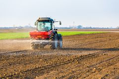 Farmer fertilizing arable land with nitrogen, phosphorus, potassium fertilizer. Agricultural activity Royalty Free Stock Photo