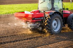 Farmer fertilizing arable land with nitrogen, phosphorus, potassium fertilizer. Agricultural activity Royalty Free Stock Photography