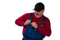 Farmer fiddling with the fastener on his bib. Farmer or worker fiddling with the fastener on his bib overalls as he attempts to dress or undress isolated on stock photos
