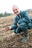 Farmer in field holding earth Royalty Free Stock Images