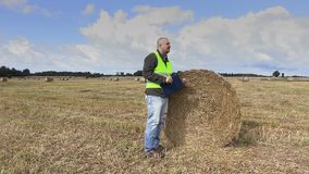 Farmer on the field near straw bale stock video