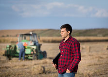 Farmer in field with tractor in background Stock Photography