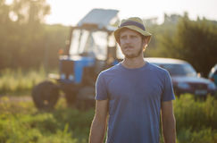Farmer on the field with the tractor on the background at organic farm. Portrait of young farmer in hat on the field in sunset light with the tractor on the Royalty Free Stock Image