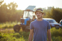 Farmer on the field with the tractor on the background at organic farm. Portrait of young farmer in hat on the field in sunset light with the tractor on the Stock Photo