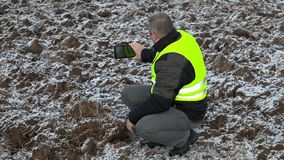 Farmer filmed with tablet PC frozen field stock footage