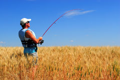 Farmer fishing for wheat. A farmer in wheat field fishing for good crop Stock Photo