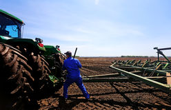 Farmer fixing a tractor. A farmer repairing farm equipment in a cultivated field Royalty Free Stock Photo