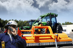 Farmer in front of giant tractor Royalty Free Stock Photos