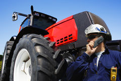 Farmer in front of giant tractor Stock Photo